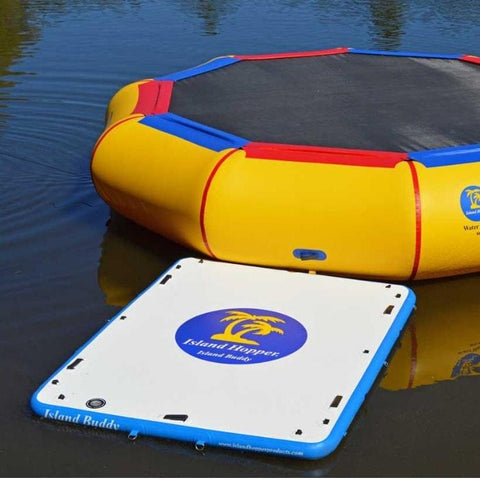 An Island Hopper Island Buddy Inflatable Floating swim platform sits connected to an Island Hopper water trampoline on a lake.  The white and blue Island Buddy inflatable floating dock rests easy on the glass-like dark blue water.