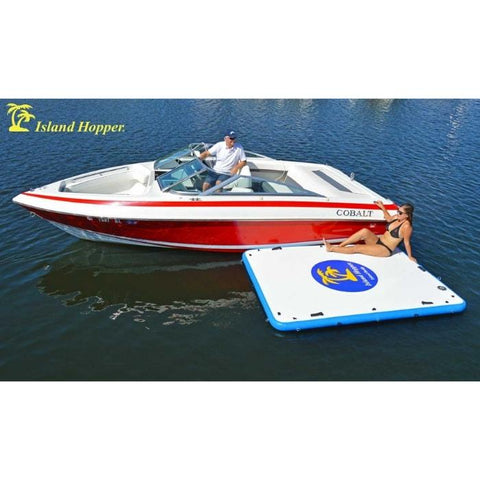 Island Hopper Island Buddy Inflatable Floating swim platform is tied up to a boat while a woman kicks back and relaxes.  The red boat is sitting idle in the water while the white and blue floating swim platform rests against it.
