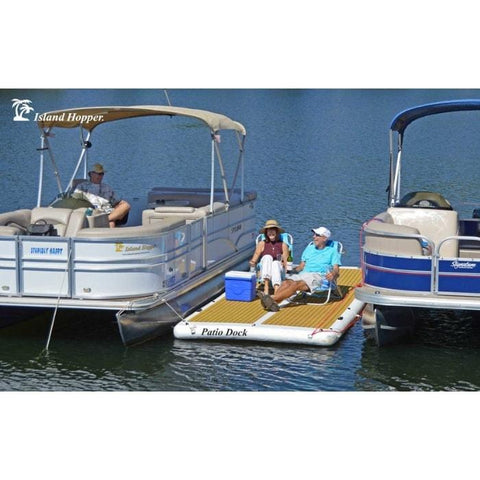 The Island Hopper Patio Dock Floating Swim Platform is shown here attached in between 2 pontoon boats.  There are 2 people sitting in chairs on the inflatable floating dock along with a cooler.  The water is dark blue and is visible in front and behind the inflatable dock and the boats.
