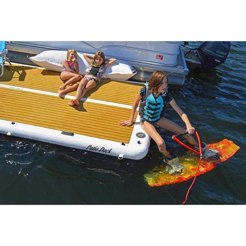 Island Hopper Patio Dock Floating Swim Platform makes a great launch point for wakeboarding.  Here you see a couple of girls laying down on the inflatable floating dock while a young boy sits on the edge with his feet braced into a wakeboard waiting to take off.