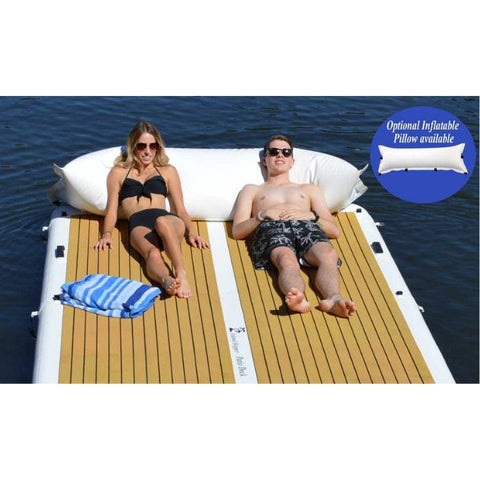 Island Hopper Patio Dock Floating Swim Platform is great for sun tanning.  A young boy and young woman are laying on the inflatable floating dock with a big inflatable pillow.  The tan eva foam non-slip surface looks great with the white inflatable dock border and a strip of white down the middle.