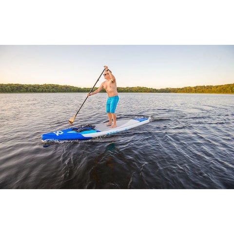Man paddling a Rave Nomad 6 Inflatable Stand Up Paddle Board on a lake.  Blue nose with light grey standing pads.