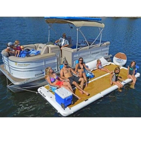 Island Hopper Inflatable Dock for Sale Floating Swim Platform is shown attached to a pontoon with 6 people relaxing and enjoying a day on the water. There are people sitting directly on the EVA foam surface and there are also people in chairs sitting on the inflatable floating dock as well as a cooler.