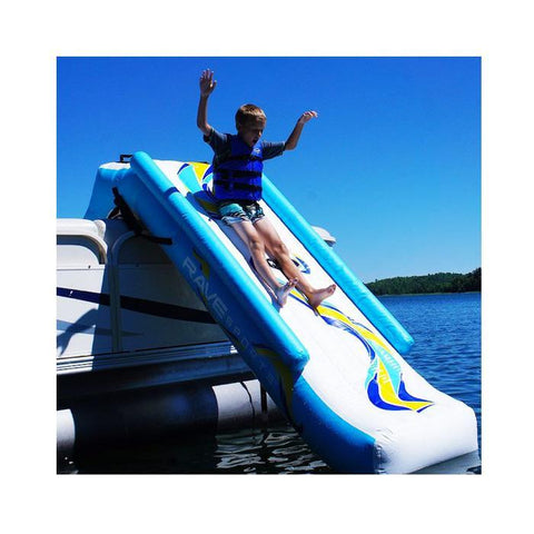 A young boy slides down the Rave Inflatable Pontoon Slide on a lake.