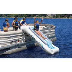 Side view of a girl sliding down a Rave Inflatable Pontoon Slide with 3 kids standing on the pontoon.  Sliding into the lake.