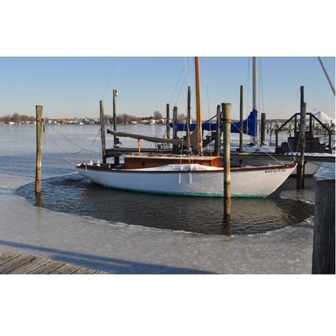 Powerhouse 250 1/4 Hp, 115v Ice Eater dock bubbler system in use around a docked sailboat in a marina.   The de-icer has gotten prevented ice from forming around the boat but there is ice in the rest of the harbor.