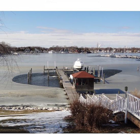 P250 PowerHouse .75 Hp Ice Eater Dock De Icer melting ice around a dock.  The rest of the lake that is visible, which is an entire cover, is all frozen except where the PowerHouse Ice Eater De-Icer is in use.