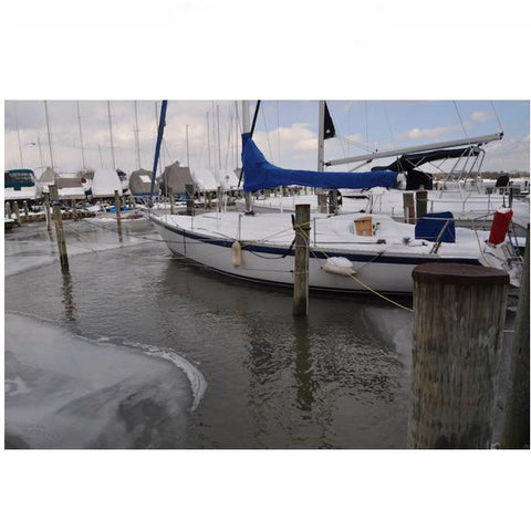 The Power House Inc 1 Hp Ice Eater dock bubbler system melting ice around a sailboat docked in a marina.  There is ice in other parts of the lake near the dock, but the deicer melts everything around the sailboat.