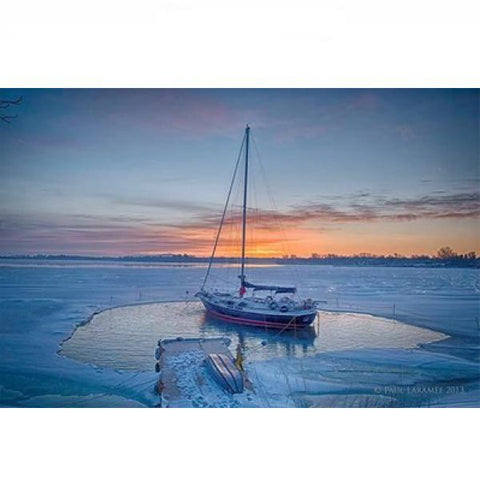 Power House Ice Eater for Sale melting ice around a sailboat moored out in a lake.  The PowerHouse Ice Eater is melting ice all around the sailboat.  The rest of the lake is frozen over showing how the PowerHouse Ice Eaters for Sale are the best dock deicers on the market.