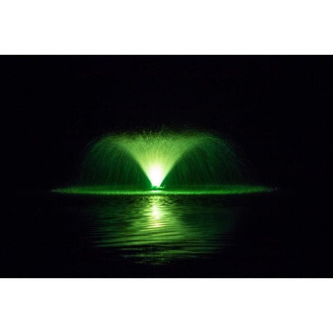 Spray of an aerating fountain is lit up in green with a color changing fountain light kit.
