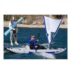Sea Eagle QuikSail - Universal Kayak Sail on the water ready to set sail. White sail with blue trim, it is in a V shape coming out of the kayak.  Inset picture of woman holding the nylon carry bag for the QuikSail.