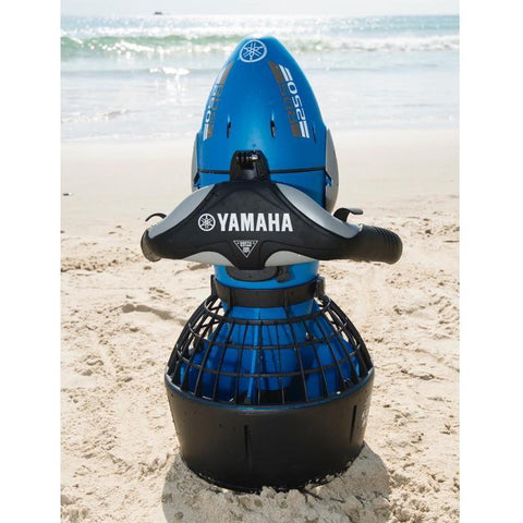 A Yamaha RDS250 Seascooter sits upright in the sand at the beach with the ocean visible in the background.  Yamaha is clearly printed in white letters across the handle bars.  There are also grey highlights on the body and handles.