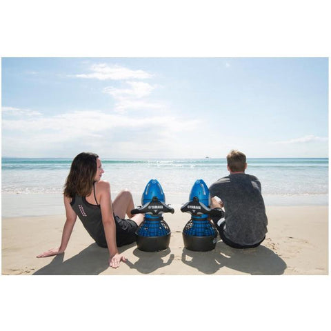 A couple sitting on the beach with their Yamaha RDS250 Seascooters.  The blue RDS250 Sea Scooters are sitting between them on the beach as they look out to sea.