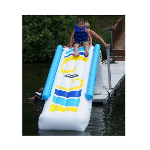 Front view of the Rave Inflatable Dock Slide.  The inflatable dock slide is white with yellow, light blue, and blue highlights on the slide.  There are inflatable light blue railings on either side. A boy is ready to slide down the inflatable water slide.