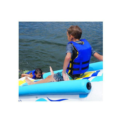 A young boy begins his slide down the rave inflatable dock slide into the lake.