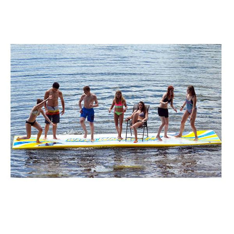 Rave Water Whoosh 15 Floating Water Mat on the lake with 6 people standing and playing and one girl sitting in a chair on the sturdy inflatable water mat.  The floating swim mat is white and yellow with blue highlights.