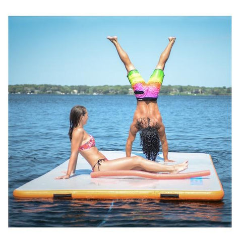 A guy does a handstand on the Mission Reef inflatable water mat while a girl sits by and watches.  The inflatable water mat is on the lake on a beautiful day.