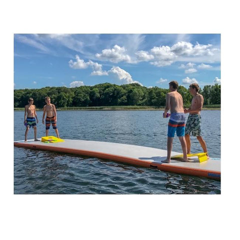 4 people stand on the Mission Reef-129 Inflatable Floating Dock playing a game of cornhole. The inflatable water mat for lakes is perfectly steady on the water.