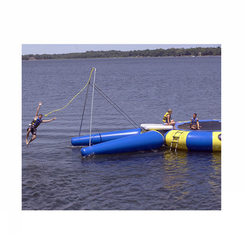 Man letting go over the rope on a Blue Rave Rope Swing Water Trampoline Attachment attached to a blue and yellow Rave Water Trampoline.  Rope Swing water trampoline attachment is on a dark lake against a blue sky.