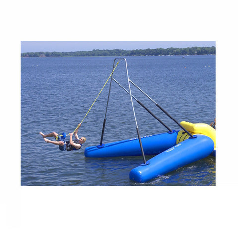 Man swinging on the Rave Rope Swing Water Trampoline Attachment in the middle of the lake.  Rave Rope Swing features blue inner tubes with yellow highlights and an aluminum swing frame with black padding on the bottom portions of the frame.