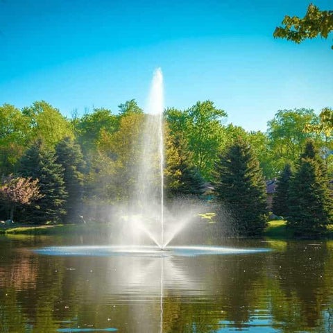 Beautiful Scott Aerator Skyward Pond Fountain 1 1/2 Hp as a large pond fountain. Beautiful white water sprays vs the background of trees, also reflecting off the dark blue and earth tone lake waters.
