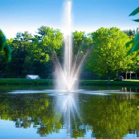 Scott Aerator Atriarch Pond Fountain sits in the middle of pond creating a beautiful spray of water up in the air against green trees in the background.  The Scott Aerator Floating Pond Fountain elegance is on display. This floating fountain is a spectacular sight to see.