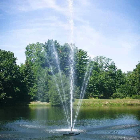 Scott Aerator Clover Pond Fountain 1 1/2 Hp sprays a 40ft water display for all to see.  The floating pond fountain is in the middle of the pond against a beautiful green tree background.