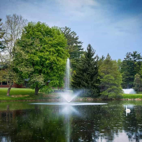 Profile shot of the Scott Aerator Skyward Pond Fountain 1 1/2 Hp sprays water in the air on a golf course lake.  Small pond fountain