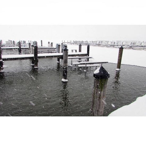A marina is shown with a deicer in the water.  The water is not frozen in the wooden dock slips but is frozen away from the dock.