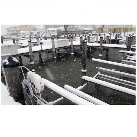 Docks in a marina are shown with a de-icer in use.  The water is not frozen in the wooden dock slips but is frozen away from the dock.