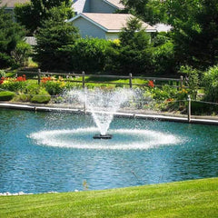 Scott Aerator DA-20 Display Aerator 1 1/2 Hp floating pond fountain creates a beautiful symmetrical water display as shown in this backyard pond with vegetation and yard around the floating fountain. This large pond aerator is also known as a Floating Pond Aerator Fountain.