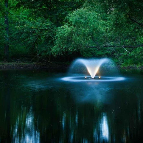 Scott Aerator DA-20 Display Aerator 3/4 Hp floating pond fountain with LED lights is a small pond aerator fountain.  Here it is shown in a somewhat dark area but still a light reflection off the water.  Forestry is in the background.