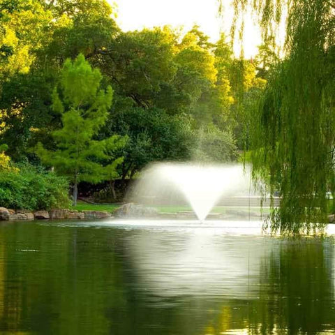 Scott Aerator DA-20 Display Aerator 3 Hp Floating Pond Fountain.  This large pond aerator is also known as a Surface Aerator Fountain and is shown as the sun sets behind the green trees as the large pond aerator tranquilly sprays.