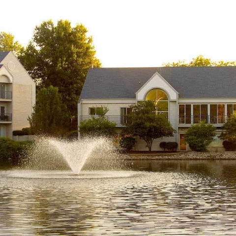 This large pond aerator, the Scott Aerator Display Aerator 2 Hp. This large pond aerator is also known as a Floating Pond Aerator Fountain.  Here it is used in a large neighborhood pond and there are houses in the background of the floating pond fountain aerator.