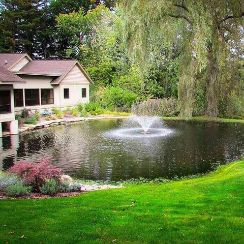 Scott Aerator DA-20 Display Aerator 1/3 Hp Floating Pond Fountain spraying a trumpet shaped water fountain spray in the middle of a neighborhood lake.  5ft tall floating fountain spray. Also known as a Small Pond Aerator Fountain.