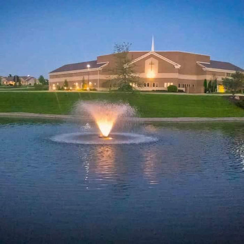 Amazing view of the Scott Aerator Display Aerator 1 1/2 Hp floating pond fountain as a pond aerator with light kit with a large building in the background. This large pond aerator is also known as a Floating Pond Aerator Fountain.