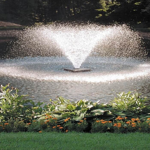 Scott Aerator DA-20 Pond Aerator 1/2 Hp floating pond fountain in a pond spraying a trumpet shaped water fountain.  The floating pond aerator has grass and landscaping around. Also known as a Small Pond Aerator Fountain.