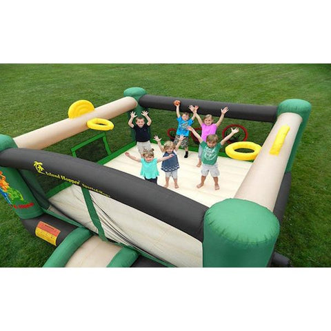 Top view of kids playing in the Island Hopper Sports and Hops 5 Bounce House showing the tan bounce floor, tan slide, yellow basketball hoop, black inflatable support beams, and green support towers.