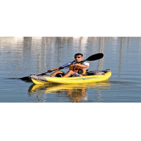 Man calmly paddling a yellow Advanced Elements StraitEdge Solo Inflatable Kayak on the open water.