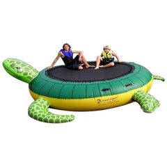 A lady and young boy sitting on the Island Hopper Turtle Hop Water Bouncer.  The inflatable water bouncer has a green and yellow design to make it look like a turtle.  The water bouncer surface is black.  Image is on a white background.