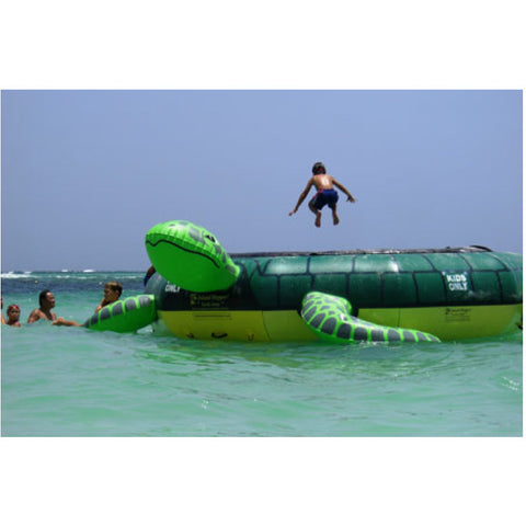 Kid jumping on an Island Hopper Turtle Jump Water Trampoline in the ocean.