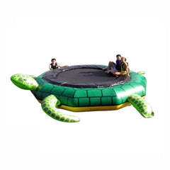2 kids sitting on the Island Hopper Turtle Jump Water Trampoline.  The inflatable water trampoline has a green and yellow design and made to look like a turtle, including turtle legs.  Black water trampoline surface.