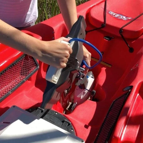 Bixpy Jet Kayak Motor for sale is shown being installed on a kayak using the Bixpy Hobie Mirage Pedal Adapter in the center of a red kayak.  A blue cable is attached and the Outboard Kayak Motor Power Pack is located on the rear of the kayak on a black surface.