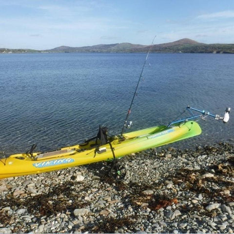Bixpy Kayak Jet Motor is shown in use with a Bixpy Universal Kayak and Canoe Adapter on a green and yellow kayak.  The Bixpy Jet Thruster is fully out of the water and the kayak is resting on the rocky shore on a stand.  The Kayak Outboard Motor Power Pack is not visible, but the blue connecting cable is.