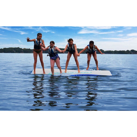 4 girls standing up on a Rave Water Whoosh 10 Inflatable Water Mat on a lake.  Rave Floating Water Mat is in the middle of the lake on a clear day with blue skies.