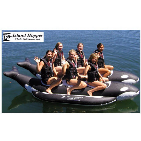 Side view of 6 girls riding an Island Hopper 6 Person Whale Ride Banana Boat Tube on the water.