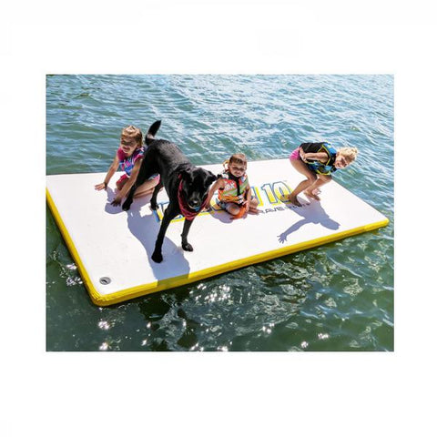 3 Young kids sitting on the Rave Water Whoosh 10 Floating Water Mat with their dog, floating on the lake.  The top of the water mat is almost all white with yellow letters and edging.