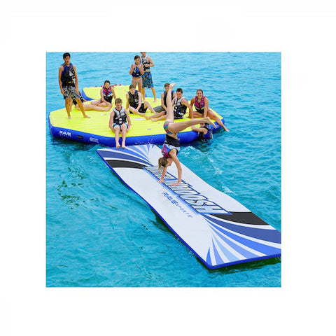 Rave Sports Water Whoosh 20' Inflatable Floating Water Mat kid doing a  cart wheel on the mat on the water attached to swim platform