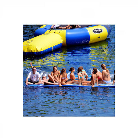 Several young adults sitting on a Rave Water Whoosh 20' Inflatable Water Mat on a lake.