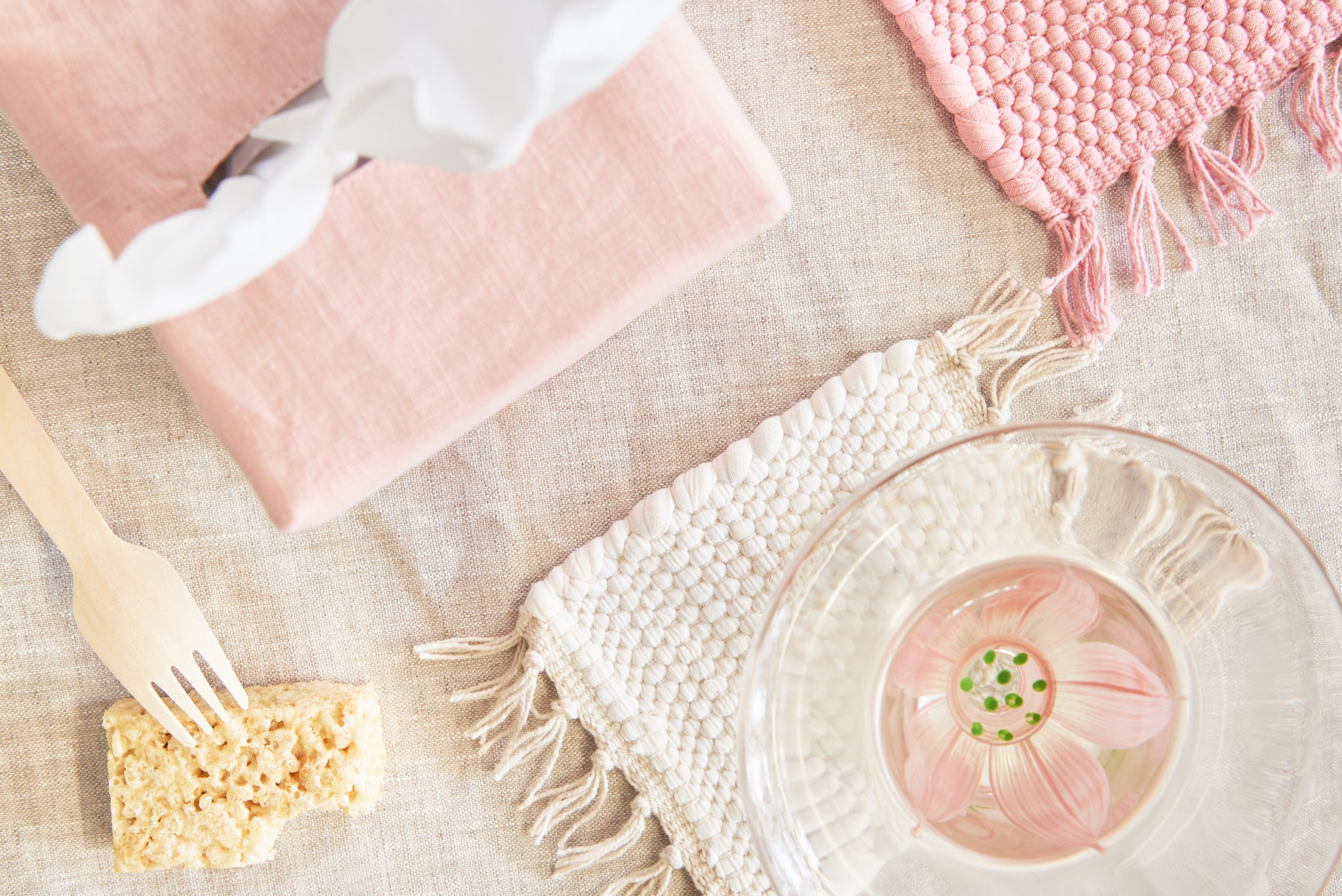 flat lay, tissue box with pink cover, rice krispie treat with wooden fork, cream rug coaster, pink rug trivet